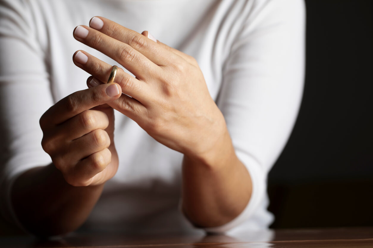 Person taking wedding ring off finger